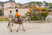 A young Mexican boy rides a donkey watched by his father in the village of Teotitlan de Valle in the Oaxaca Valley, Mexico.
