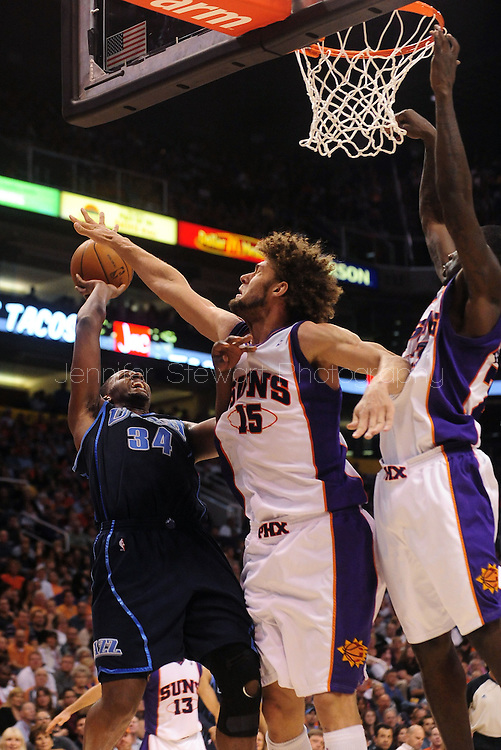 Mar. 19 2010; Phoenix, AZ, USA; Utah Jazz forward C.J. Miles (34) puts up a shot against Phoenix Suns center Robin Lopez (15) and forward Amare Stoudemire (1) in the second half at the US Airways Center.  The Suns defeated the Jazz 110-100. Mandatory Credit: Jennifer Stewart-US PRESSWIRE.
