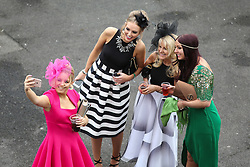 © Licensed to London News Pictures. 09/04/2016. Liverpool, UK. A group of brightly dressed ladies take a selfie on Grand National day of the Grand National 2016 at Aintree Racecourse near Liverpool. The race, which was first run in 1839, is the most valuable jump race in Europe. Photo credit : Ian Hinchliffe/LNP