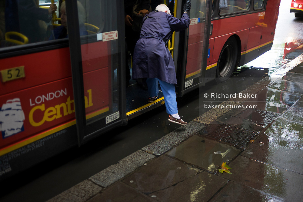 A young woman walking along a London street is about to be splashed by a passing London bus at a flooded bus stop.