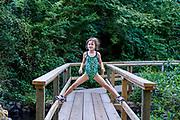 Girl posing confidently on a footbridge.