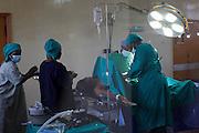 Doctor Ivan Nyenje (nearside) performing a caesarean section at Kasangati Health Centre in Uganda.