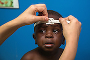 An African refugee child cries as his head circumference is measured during a wellness checkup at the Refugee Egypt health clinic in the Zamalek neighborhood of Cairo, Egypt September 21, 2016. Photo by UNHCR/Scott Nelson