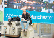 © Licensed to London News Pictures. 23/09/2014. Manchester, UK A man sits outside the conference centre. Leader of the Labour Party Ed Miliband gives his leaders speech at the Labour Party Conference 2014 at the Manchester Convention Centre today 23 September 2014. Photo credit : Stephen Simpson/LNP