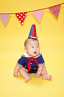 Asian baby boy wearing a sailor suit and majorette had against yellow seamless<br /> Photographed at the Photoville Photo Booth September 20, 2015
