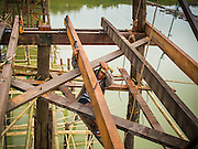 16 SEPTEMBER 2014 - SANGKHLA BURI, KANCHANABURI, THAILAND: A member of the Mon community works under the deck of the Mon Bridge. The 2800 foot long (850 meters) Saphan Mon (Mon Bridge) spans the Song Kalia River. It is reportedly second longest wooden bridge in the world. The bridge was severely damaged during heavy rainfall in July 2013 when its 230 foot middle section  (70 meters) collapsed during flooding. Officially known as Uttamanusorn Bridge, the bridge has been used by people in Sangkhla Buri (also known as Sangkhlaburi) for 20 years. The bridge was was conceived by Luang Pho Uttama, the late abbot of of Wat Wang Wiwekaram, and was built by hand by Mon refugees from Myanmar (then Burma). The wooden bridge is one of the leading tourist attractions in Kanchanaburi province. The loss of the bridge has hurt the economy of the Mon community opposite Sangkhla Buri. The repair has taken far longer than expected. Thai Prime Minister General Prayuth Chan-ocha ordered an engineer unit of the Royal Thai Army to help the local Mon population repair the bridge. Local people said they hope the bridge is repaired by the end November, which is when the tourist season starts.    PHOTO BY JACK KURTZ