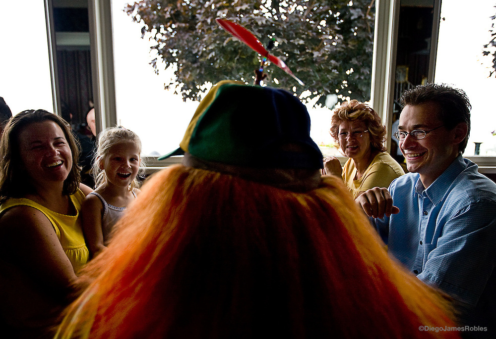 "A family laughs at Scooter's jokes and enjoys his company during brunch. ""The wig we chose to use are made from yak hair,"" Jim said proudly of his and his wive's hair apparel. ""The musical Cats used yak hair because it can be dyed well and styled."""