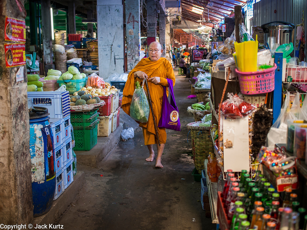 01 APRIL 2014 - BANGKOK, THAILAND: A Buddhist monk walks through the Bangkok flower market. This part of the market is being renovated into a high end mall. The Yodpiman Flower Market (also called Pak Khlong Talat) is being renovated and gentrified. The market opened in 1961 and has been a Bangkok landmark for more than 50 years, is being turned into a high end mall. Many of the flower and vegetable vendors in the market may be forced out.    PHOTO BY JACK KURTZ
