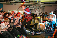 Randy Randall of No Age, center, performs while playing guitar.  Ed Schrader opens. Dan Deacon plays a show with Ed Schrader, No Age, Deer Hunter and Dan Deacon play a show at Rhino's All Ages Club 5 Aug 2009. The show was a round robin.