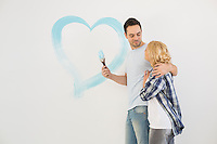 Loving mid-adult couple with painted heart on wall