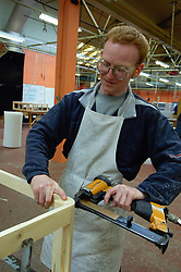 Remploy factory; Forest Hall; Newcastle; UK 2007, Remploy provides specialist employment services to disabled people and those who face barriers to employment, Man making bed base; fastening corners