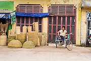 14 JUNE 2013 -  PATHEIN, AYEYARWADY, MYANMAR: A pedicab driver waits for a fare in front of a building in Pathein. Pathein, sometimes also called Bassein, is a port city and the capital of the Ayeyarwady Region, Burma. It lies on the Pathein River (Bassein), which is a western branch of the Irrawaddy River. It's the fourth largest city in Myanmar (Burma) about 190 km west of Yangon.   PHOTO BY JACK KURTZ