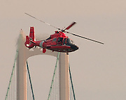 A Coast Guard helicopter searches the waters of the Straits of Mackinac for a woman who jumped from the Mackinac Bridge.