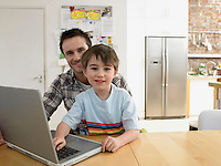Boy (3-6) using laptop with father in kitchen (portrait)