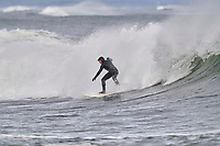 Winter surfers riding waves Cherry Hill, Arties Cove, Nova Scotia, Canada.