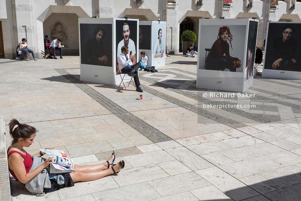 City workers enjoy spring sunshine during their lunch hours at the Guildhall, next to an outdoor photography exhibition on the theme of mental health, in the City of London, the capital's ancient, financial district, on 14th May, in London, England. Located in the courtyard of Guildhall Yard, Let's Talk is a collaboration between photographer Charlie Clift and artist Kate Forrester. It takes the form of a series of large photographs of celebrities. (Photo by Richard Baker / In Pictures via Getty Images)