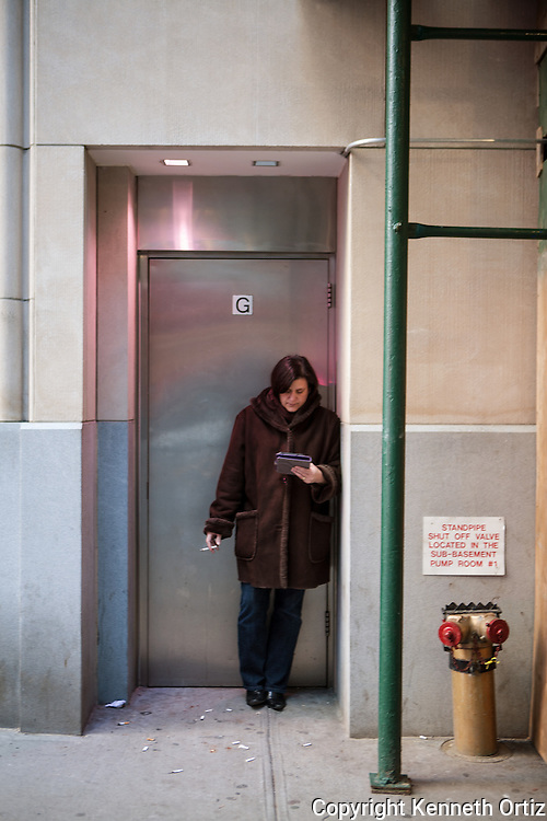 A woman reading her Kindle and taking a smoke break on 42nd Street between 6th & 7th Avenue's in New York City.