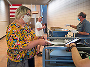 02 JUNE 2020 - WEST DES MOINES, IOWA: A voter wearing a face mask slides her ballot into a machine to be counted on primary election day at Valley High School in West Des Moines. Because of the Coronavirus pandemic, all of the polling places in West Des Moines were consolidated to Valley High School, where voting booths were set up with social distancing in mind and booths were sanitized before they were reused. Although Iowa uses a caucus system to select presidential candidates, they use a primary election to select candidates for other offices. Statewide, the most watched race Tuesday is the Democratic Senate primary to select a candidate to run against Republican incumbent Joni Ernst.      PHOTO BY JACK KURTZ