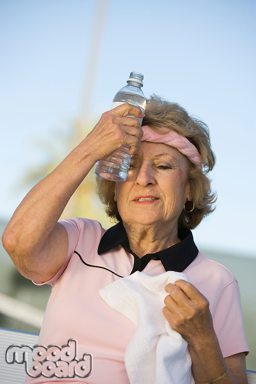 Female tennis player putting bottle of water to forehead