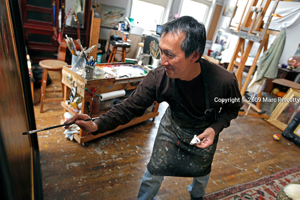 SHOT 12/22/09 12:59:46 PM - Artist Quang Ho, 46, of Littleton, Co. painting in his studio at the Art Students League of Denver space. Ho specializes in everything from still lifes to landscapes to figures and started drawing as early as age four. He is often kept company while he works by his two basset hounds 'Putter', a three year old male, and 'Birdie', a one and half year old female. (Photo by Marc Piscotty / © 2009)
