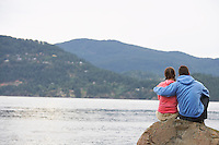 Couple embracing on rock by ocean