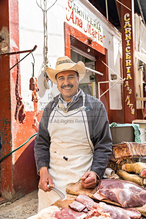 A butcher poses outside his market stall in the municipal market in Angangueo, Michoacan, Mexico. Angangueo is a tiny, remote mountain town and the entry point to the Sierra Chincua Monarch Butterfly Sanctuary.