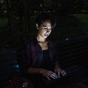 Ragazza con computer portatile sulla panchina di un parco pubblico, il viso illuminato dalllo schermo del computer...A girl with a laptop on a public garden bench, the face lit up by the laptop screen.