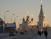 Passanten vor einer russisch orthodoxen Kirche in der Innenstadt von Jakutsk. Jakutsk wurde 1632 gegruendet und feierte 2007 sein 375 jaehriges Bestehen. Jakutsk ist im Winter eine der kaeltesten Grossstaedte weltweit mit durchschnittlichen Winter Temperaturen von -40.9 Grad Celsius. Die Stadt ist nicht weit entfernt von Oimjakon, dem Kaeltepol der bewohnten Gebiete der Erde.<br /> <br /> Passersby infront of a Russian Orthodox church in the city center of Yakutsk. Yakutsk was founded in 1632 and celebrated 2007 the 375th anniversary - billboard announcing the celebration. Yakutsk is a city in the Russian Far East, located about 4 degrees (450 km) below the Arctic Circle. It is the capital of the Sakha (Yakutia) Republic (formerly the Yakut Autonomous Soviet Socialist Republic), Russia and a major port on the Lena River. Yakutsk is one of the coldest cities on earth, with winter temperatures averaging -40.9 degrees Celsius.