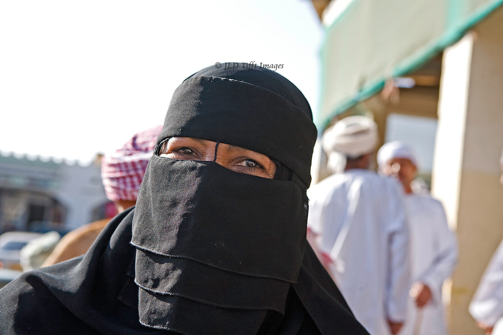 Market day in the Sinaw souk, Oman.  Livestock (goats, camels), vegetables, and weapons on offer.  Men and women shoppers. Portrait of a woman wearing a black birka, or mask.