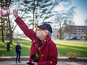 "08 APRIL 2020 - DES MOINES, IOWA: A resident of Summit House wearing a face mask stands on the front lawn of the building and waves at her neighbors. Summit House is a condominium building for older adults. Residents are practicing ""social distancing"" and always wear masks when they go outside of their units. On Wednesday evenings they stand on their porches for a few minutes to wave at passing cars and socialize. On Wednesday, 08 April, Iowa reported 1,145 confirmed cases of the Novel Coronavirus (SARS-CoV-2) and COVID-19. There have been 27 deaths attributed to COVID-19 in Iowa. Most non-essential businesses are closed until 30 April. There have been outbreaks of Coronavirus in several Iowa senior citizen housing complexes.        PHOTO BY JACK KURTZ"
