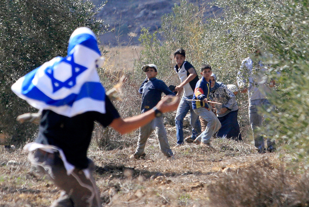 An Israeli settler masked with an Israeli flag and Palestinian men  throw on each others stones  during clashes on a Olives harvest close to Havat Gilad on October Wednesday  25. 2006...Photo by Olivier Fitoussi .