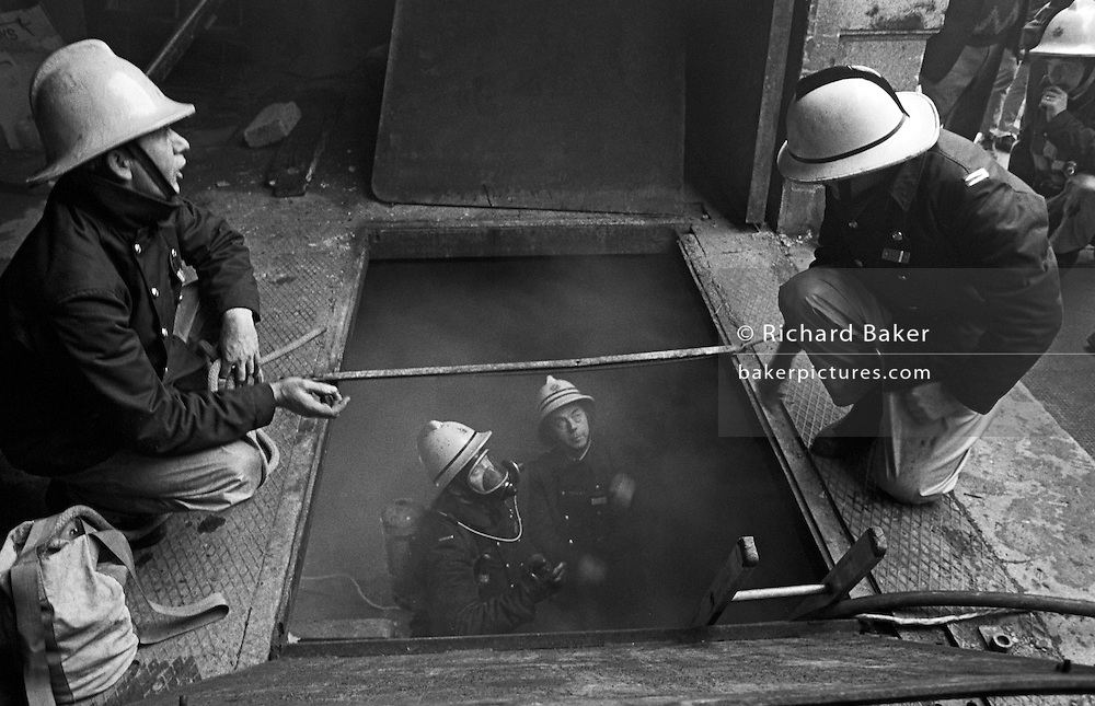 Smoke has been discovered in the basement of a shop in Market Street, Newport town centre, south Wales. We look down into a dark hole where two fire fighters - one of which is a senior officer, with two stripes on his helmet - have gone down a ladder to find the source of the smoke while wearing breathing apparatus (BA) as a precaution.  While looking up they discuss the possibilities of a seat of fire elsewhere so they talk to their colleagues who crouch over the open floor of the business who dialled 999 for the fire brigade to attend this incident. It is 1984 and the firemens' equipment looks dated, during an era when uniform material was not of a high fire-retardant specification and nor were their helmets which went through important design changes.