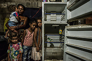 "CUMANA, VENEZUELA - JUNE 16, 2016: Leidy Cordova, a 37-year-old mother, poses for a portrait with four of her five children: Abran, 1, Deliannys, 3, Eliannys, 6, and Milianny, 8-years old. The entire family went the entire day without eating.  They had not eaten since lunchtime the day before - a soup made by boiling chicken skin and fat, that is sold for a much cheaper price than chicken at their local butcher shop. Inside their home, a broken refrigerator was empty except for half a bag of corn flour and a bottle of vinegar. That was the only food they had in their entire house, and Ms. Cordova was worried if she would be able to find a way to feed her children the next day. ""My kids tell me they're hungry,"" said Ms. Cordova as her family looked on. ""And I all can say to them is to grin and bear it."""