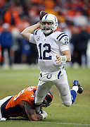Indianapolis Colts quarterback Andrew Luck (12) dodges scrambles away from pressure and a hold on his leg by Denver Broncos defensive end Derek Wolfe (95) as he falls to the ground while throwing and completing a second quarter pass during the NFL week 19 AFC Divisional Playoff football game against the Denver Broncos on Sunday, Jan. 11, 2015 in Denver. The Colts won the game 24-13. ©Paul Anthony Spinelli