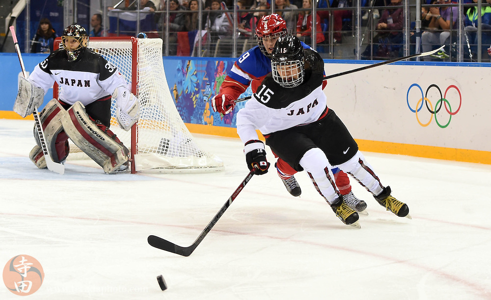 Feb 16, 2014; Sochi, RUSSIA; Japan forward Rui Ukita (15) chases after the puck with Russia forward Alexandr Vafina (9) in a women's ice hockey classifications round game during the Sochi 2014 Olympic Winter Games at Shayba Arena.
