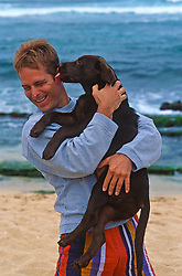 Man being licked on the ear by a chocolate lab puppy at the beach in Maui, Hawaii