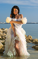 Young and sensual woman looking at camera posing with a wedding dress in the beach