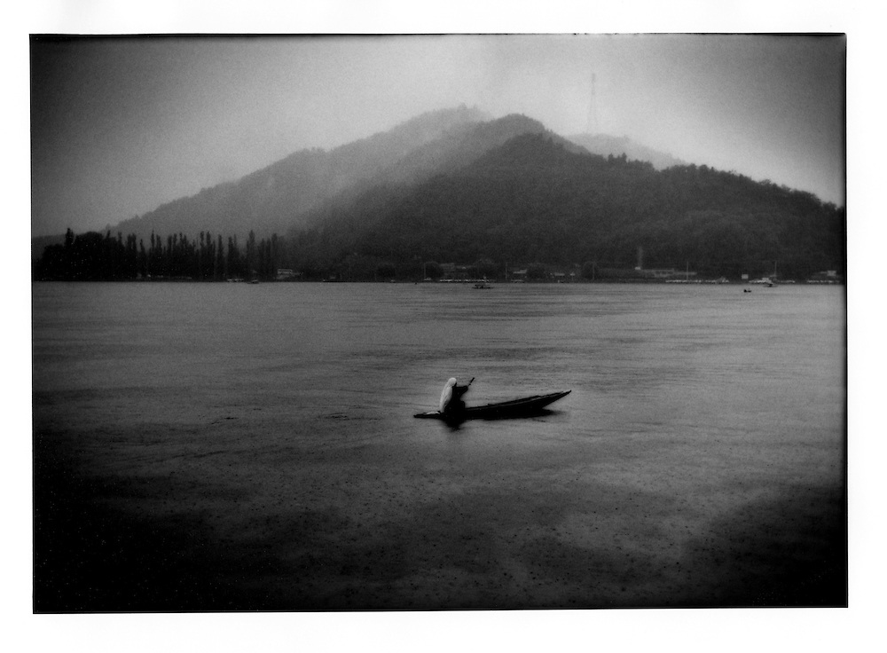 Kashmiri woman paddles through a cloudburst, Dal Lake, Srinagar, Indian Administered Kashmir.