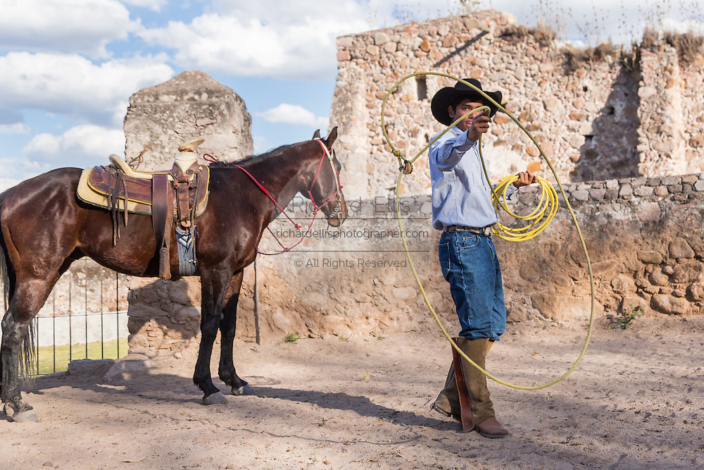 A Mexican charro or cowboy practices roping skills with his horse at a hacienda ranch in Alcocer, Mexico. The Charreada is a traditional Mexican form of rodeo and tests the skills of the cowboy at riding, roping and controlling cattle.