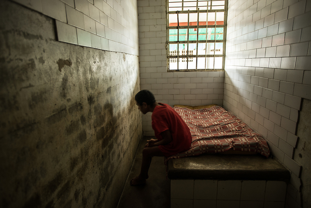 BARQUISIMETO, VENEZUELA - JULY 28, 2016: Iris Rodríguez, a patient who suffers from organic psychosis and mental retardation, and who was abandoned by her family,  rocks back in forth for hours at a time in her solitary confinement cell. She is not violent, but the nursing staff keeps her locked in isolation because she eats things that she shouldn't when she is left to roam around the women's ward and patio with other patients. The economic crisis that has left Venezuela with little hard currency has also severely affected its public health system, crippling hospitals like El Pampero Psychiatric Hospital by leaving it without the resources it needs to take care of patients living there, the majority of whom have been abandoned by their families and rely completely on the state to meet their basic needs. PHOTO: Meridith Kohut