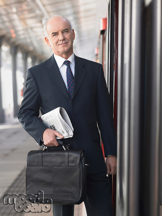 Mature Businessman holding briefcase and newspaper standing outside train in empty Train Station