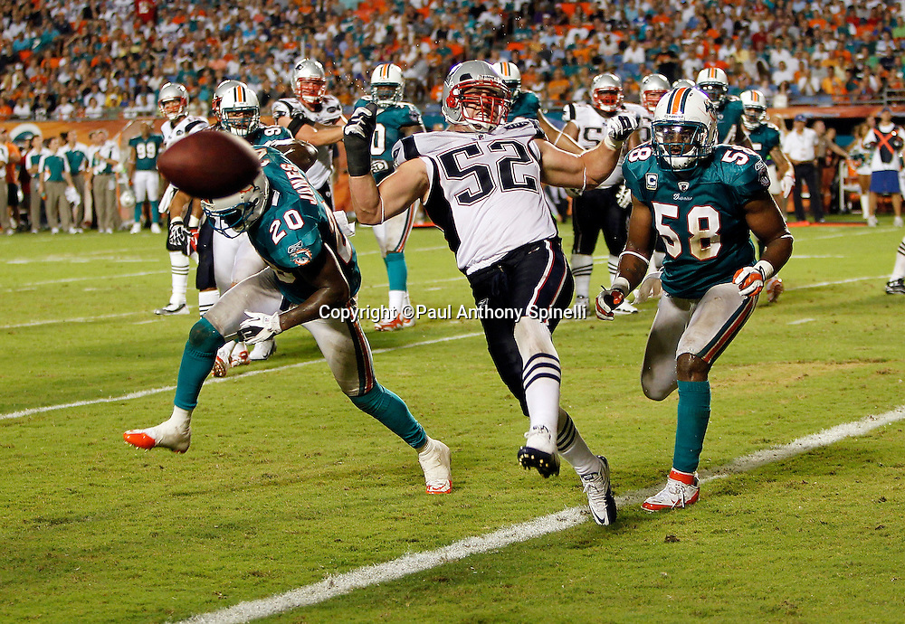 New England Patriots linebacker Dane Fletcher (52) grimaces on an incomplete pass defended by Miami Dolphins defensive back Reshad Jones (20) and Miami Dolphins linebacker Karlos Dansby (58) during the NFL week 1 football game against the Miami Dolphins on Monday, September 12, 2011 in Miami Gardens, Florida. The Patriots won the game 38-24. ©Paul Anthony Spinelli