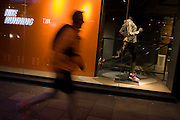 Jogger runs past Nike shop window in central London.