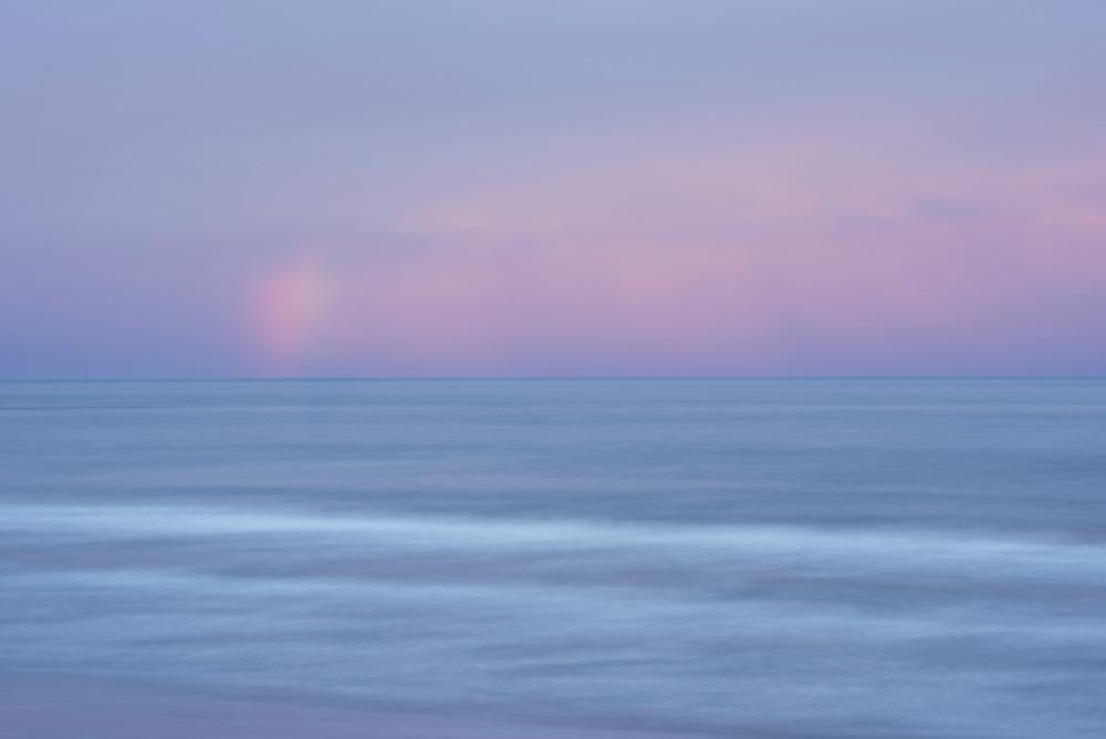 Rainbow over ocean at sunrise; Kalaloch Campground beach, Olympic National Park, Washington.