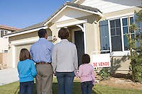Family with two children (6-8) in front of new house, back view