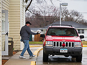 """18 MARCH 2020 - DES MOINES, IOWA: CODY EVISON, at the South Side Senior Center in Des Moines, brings hot food to a waiting client. Des Moines senior centers closed their dining rooms this week in response to the Coronavirus. Clients are picking up their meals on a """"drive through"""" basis. On Wednesday morning, 18 March, Iowa reported 29 confirmed cases of the Coronavirus. Restaurants, bars, movie theaters, places that draw crowds are closed for at least 30 days. There are no """"shelter in place"""" orders in effect anywhere in Iowa but people are being encouraged to practice """"social distancing"""" and many businesses are requiring or encouraging employees to telecommute.     PHOTO BY JACK KURTZ"""