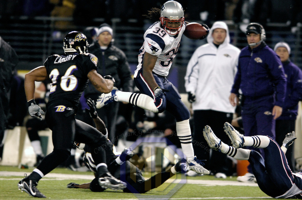 The New England Patriots running back Laurence Maroney (39) runs for a 36-yard gain in the 3rd quarter and leaps over Baltimore Ravens cornerback Samari Rolle (22) as safety Dawan Landry (26) closes in on December 3, 2007 at M&T Bank Stadium in Baltimore, Maryland.  The Patriots defeated the Ravens 27-24.