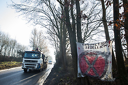 Harefield, UK. 21 January, 2020. Vehicles pass an Extinction Rebellion banner at the roadside site of the Save the Colne Valley Stop HS2 wildlife protection camp on Harvil Road. Activists reoccupied the field behind the roadside camp on 18th January in order to seek to protect ancient woodland set to be destroyed by HS2.