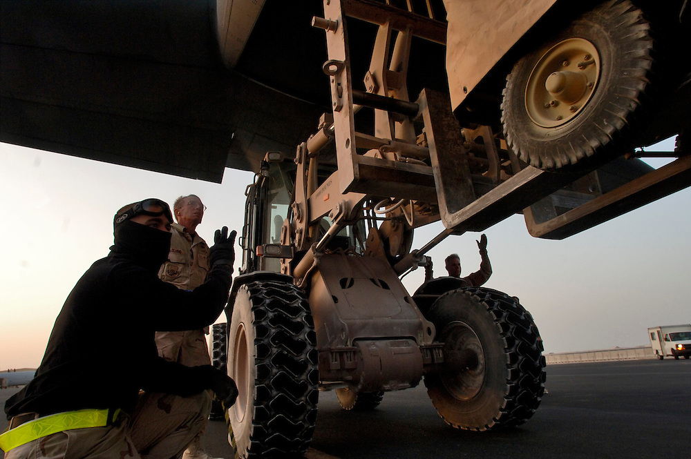 SOUTHWEST ASIA (AFPN) ? Airman 1st Class James Barclay (left), and McClung an air transportation ramp personnel, monitors a wheel chock and the movement of the forklift, loaded with an EALS regulators trailer. Airman John Meeker is at the controls of the forklift under the tail of the C-130J Hercules cargo aircraft. And Senior Airman Marc Garnsey (right) is giving hand signals to Meeker whos forward vision is blocked by the cargo. The J-model is the latest addition to the C-130 fleet. It incorporates state -of--the-art technology to reduce manpower requirements, lower operating costs, and provides life-cycle cost savings over earlier C-130 models. Its distinctive 6-bladed composite propeller coupled to a Rolls-Royce AE2100D3 turboprop engine brings substantial performance improvements. The four engines, each rated at 4.700 horsepower enable the aircraft to fly 5,000 feet higher (28,000 feet) and 50 mph faster (417 mph) than the preceding H-model.  (U.S. Air Force photo by Master Sgt. Lance Cheung)<br />