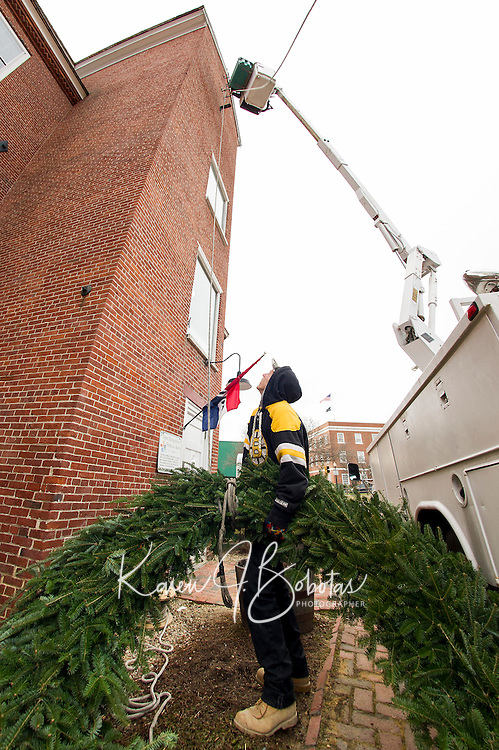 Holidayt wreath donated by Opechee Garden Club being hung at the Belknap Mill by Hutchins Electric.  Karen Bobotas/for the Laconia Daily Sun